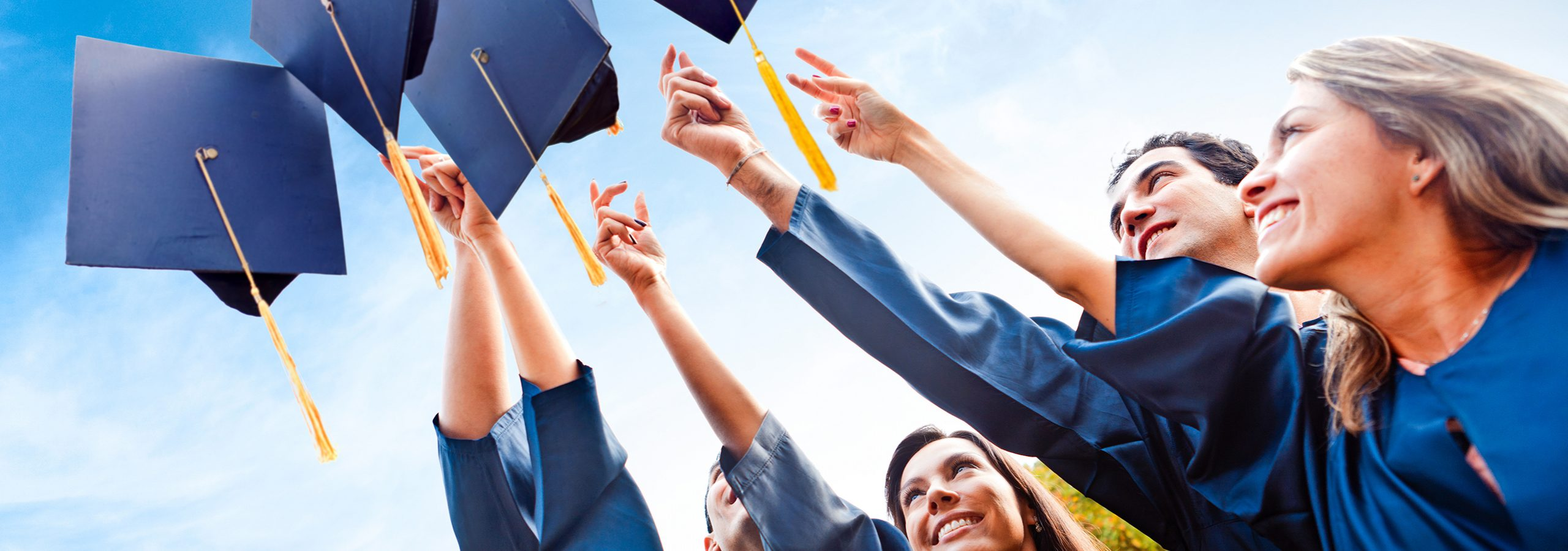 Graduates holding hat in the air